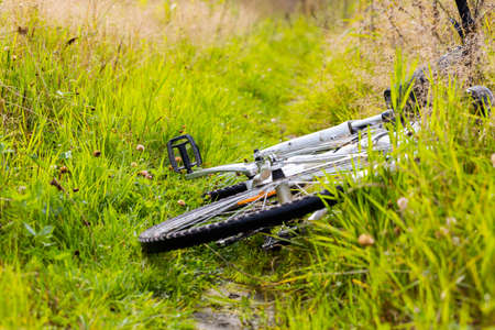 Bicycle in in the green grass close up. Wheel tire. Seasonal sports, adventure, active lifestyle and relaxation. Cycling in nature