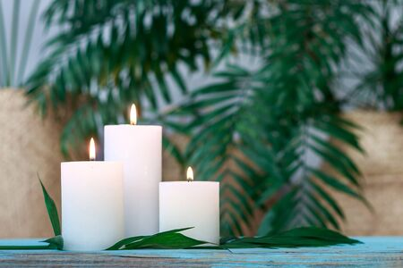 White burning candles on palm background