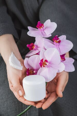 Background with blank white cream bottle and branch of beautiful pink orchids in a female hands. Branding mock-up. Vertical photo.