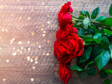 Bouquet of red roses on a wooden background with bokeh for Valentines day. 写真素材