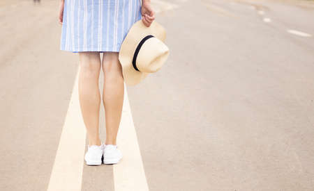 a young girl stands on the road at the dividing strip in a pink hat and white sneakers, sunset soldier, street