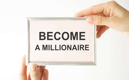 Become a Millionaire. Man holding a card with a message text written on it