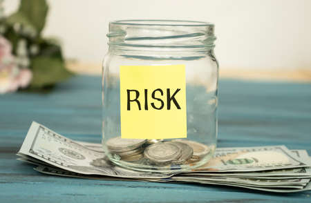 paper with the text RISK on a glass jar with coins standing on dollar bills.