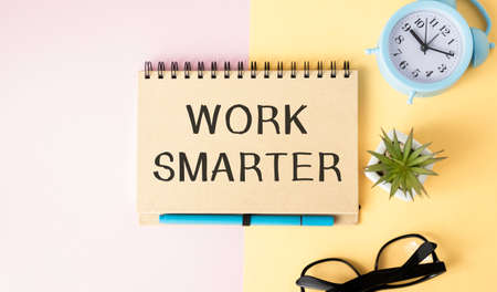 WORK SMARTER written on a light background near a computer, flower, glasses, magnifier and paper clips