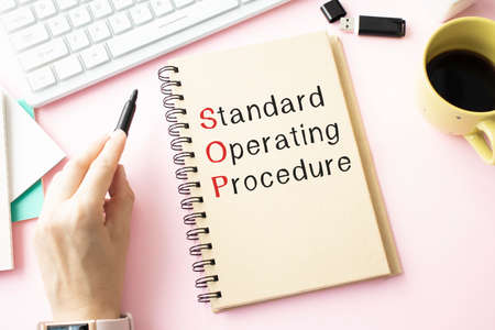 Standard Operating Procedure text on paper in open diary with spectacles, colorful push pin, pen and calculator on the wooden table - business and finance concept