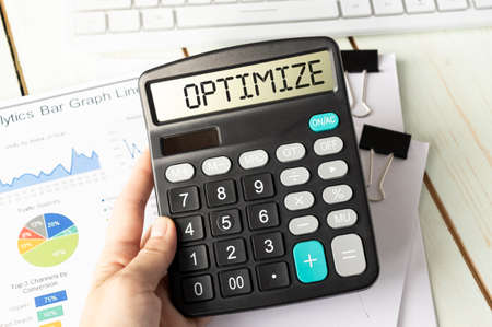 A calculator with the inscription OPTIMIZE is placed in the stack of documents. Business concept