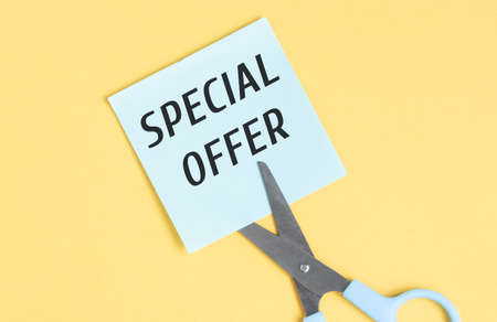 Special offer banner text on paper. Scissors cut the paper with the text. Stockfoto