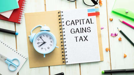 Capital gains tax-text label in the form of a document Registrar planning folder. Mandatory gratuitous payment is established by law by the state government.
