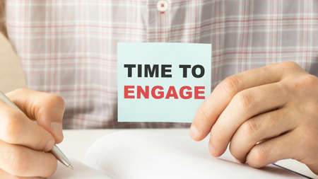 Businessman holding a card with text TIME TO ENGAGE