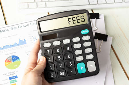 A calculator with the inscription FEES is placed in the stack of documents. Business concept