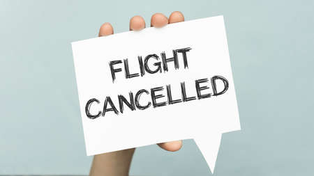 Hands hold a card with the text FLIGHT CANCELED