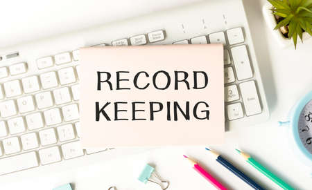 Notepad with Record keeping text on keyboard with pencils, paper clips, potted flower and alarm clock.