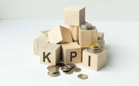 Acronym KPI - key performance indicator. Wooden small cubes with letters isolated on white background with copy space available. Business Concept image. Banque d'images