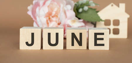 The word June on wooden cubes. Concept Month of year.