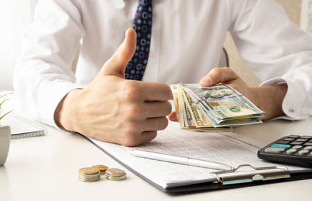 A young businessman is giving thumbs up when seeing all the money on the table in front of him.