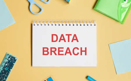 computer mouse, pens, felt-tip pens, notepad with text Data Breach on a yellow background