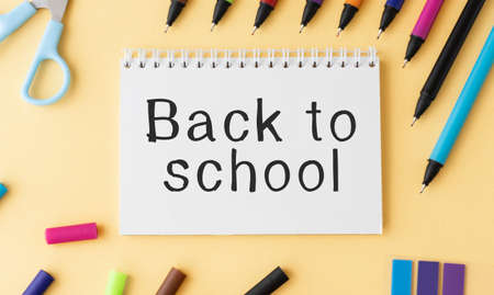 Back to school text sign on notepad with pencil and wooden plain school rulers around. Stationery and eco friendly school supplies.