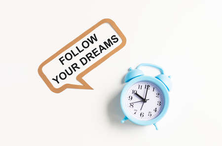 Text Follow your dreams isolated on white background with alarm clock.