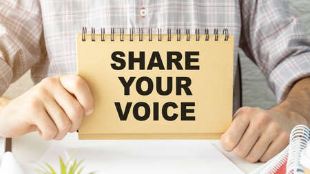 senior man holding white canvas with the phrase share your voice. concept for elders using internet and social networks.