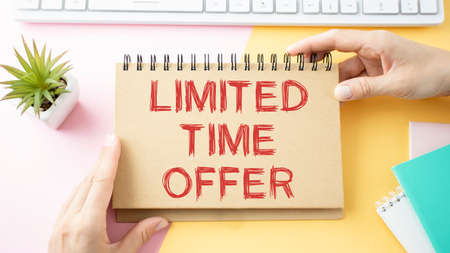 Text Limited time offer on white paper book and office supplies on blue desk, business concept