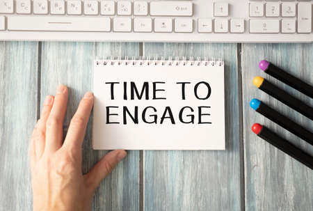Text, the word Time To Engage is written in a notebook lying on a black table with a pen and laptop. Business concept