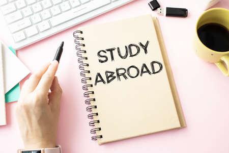 在纸上写出国外词。在国外学习在工作簿,黑背景概念的文本。