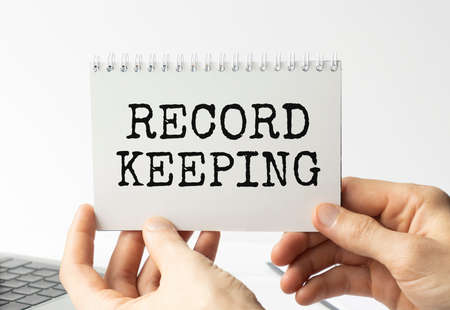 Record keeping text written on a notebook with hands.