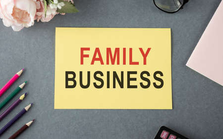 FAMILY BUSINESS text on a yellow card. gray background with office supplies. 版權商用圖片