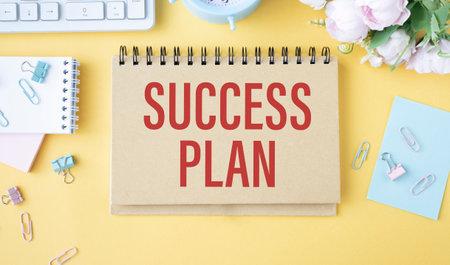 SUCCESS PLAN text is written on a yellow office board.