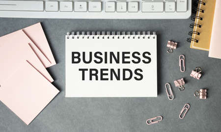 Text BUSINESS TRENDS on white paper sheet and brown paper notepad on the table with diagram.