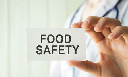 Doctor holding a card with text Food Safety, medical concept