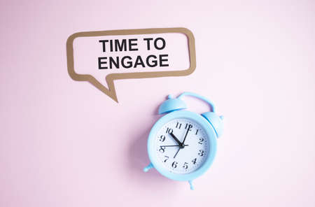 Text Time to engage on pink chalkboard near alarm clock