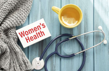 Stethoscope on note book with Women's Health words as medical concept
