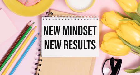 New mindset new results words letter, written on notepad, work desk top view. Motivational self development business typography quotes concept Фото со стока