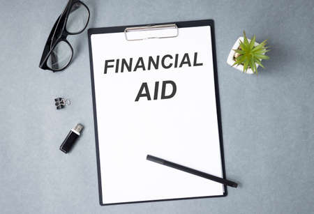 Financial Aid text written on a notebook with pencils