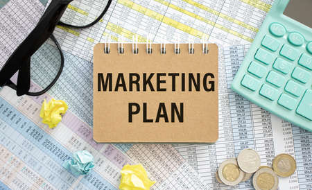 Marketing plan written on notepad, office desk with calculations and calculator, concept image for blog title or header image. Stock fotó