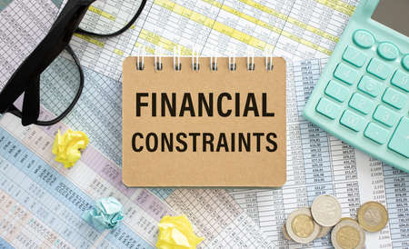 card with text FINANCIAL CONSTRAINTS, business concept image with soft focus background Stockfoto