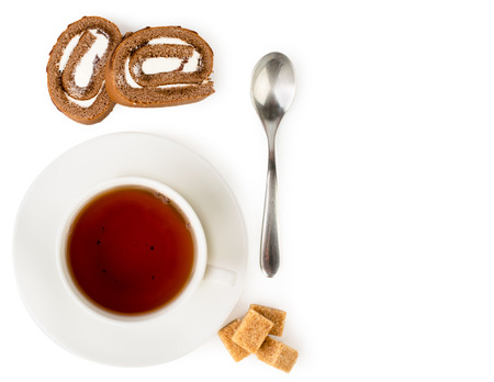 Cup of tea with pieces of biscuit roll on a white background. The view top.