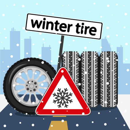 Winter tires with road sign on the road on the background of the city.