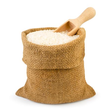 Sac de riz et cuillère en bois sur fond blanc, isolé.