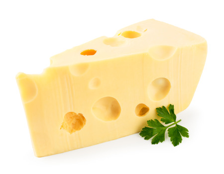 Piece of cheese with a sprig of parsley closeup on a white. Isolated.