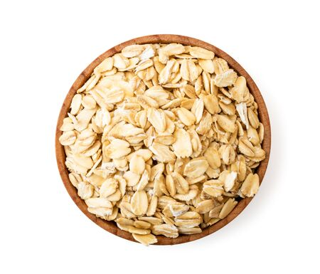 Oatmeal in a wooden plate on a white background.