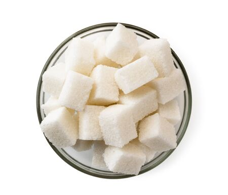 Refined sugar cubes in a glass plate on a white background. The view of the top.