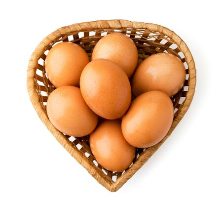 Chicken eggs in basket on a white. The view of the top.