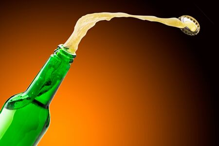 Beer splashes fly off the bottle, background. Place for text