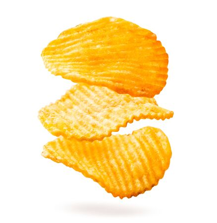 Potato chips are fluted falling on a white, isolated. Banco de Imagens