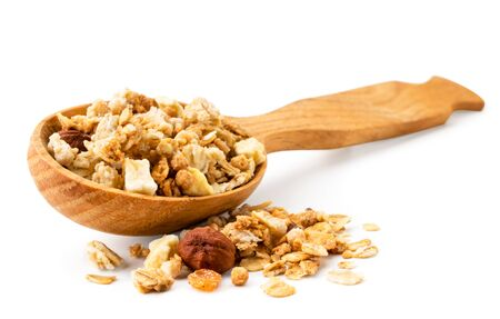 Granola spilled out from a wooden spoon closeup on a white background. Isolated Banco de Imagens