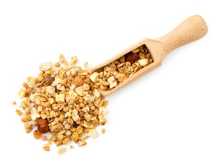 Granola with nuts spilled from a wooden scoop on a white background. The view of the top.