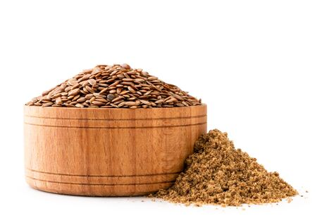 Flax seeds in a wooden plate and a pile of ground on a white, isolated.