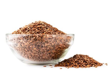 Flax seeds in a glass plate and a scattered pile on a white background.
